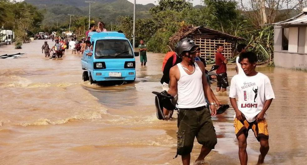Gente anda por el agua en una carretera inundada el día de Navidad en la ciudad de Ormoc, Filipinas, azotada por el tifón Phanfone. (Foto: EFE)