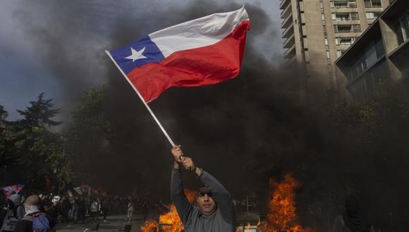 """""""De esta manera trataba de explicarle a mi hijo de 11 años lo que está ocurriendo con la economía en lugares como Chile o el Perú"""". (Photo by CLAUDIO REYES / AFP)"""
