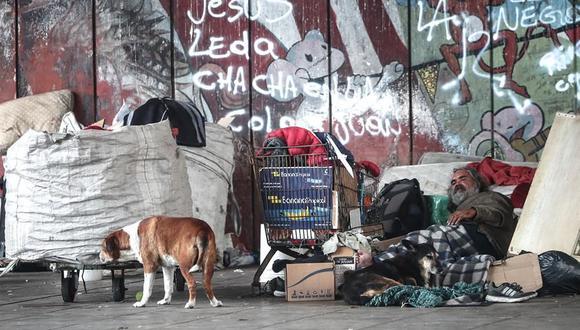 Un hombre en situación de calle descansa junto a sus perros y pertenencias en la Villa 21 de Buenos Aires, Argentina. (Foto: EFE/ Juan Ignacio Roncoroni).