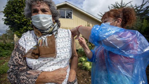 La enfermera Ximena Ampuero vacuna contra el coronavirus COVID-19 a una mujer en la isla de Chiloé, a unos 1.230 km al sur de Santiago de Chile. (Foto de ALVARO VIDAL / AFP).