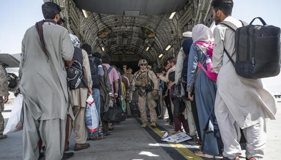 Marines de Estados Unidos guían a los evacuados a bordo de un C-17 Globemaster III de la Fuerza Aérea en el Aeropuerto Internacional Hamid Karzai en Kabul, Afganistán. (Senior Airman Brennen Lege / U.S. Air Force vía AP).