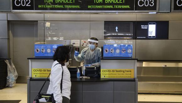 Un trabajador usa un equipo de protección personal (PPE) mientras habla con un viajero en el Aeropuerto Internacional de Los Ángeles (LAX) en Los Ángeles, California, el 18 de noviembre de 2020. (Patrick FALLON / AFP).