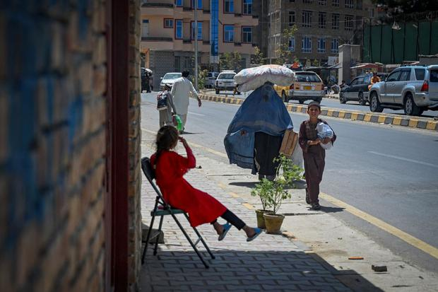 On August 7, 2021 in Kabul, a woman wearing a burqa walks with a sack over her head.