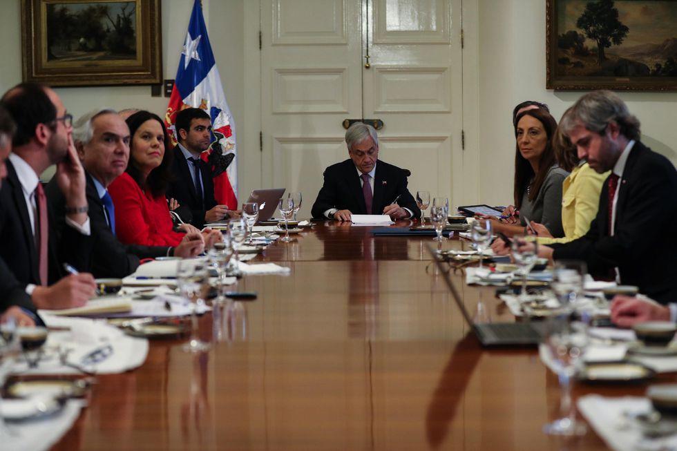 El presidente chileno Sebastián Piñera y sus ministros siguen la lectura de la sentencia desde el palacio de La Moneda. (EFE).