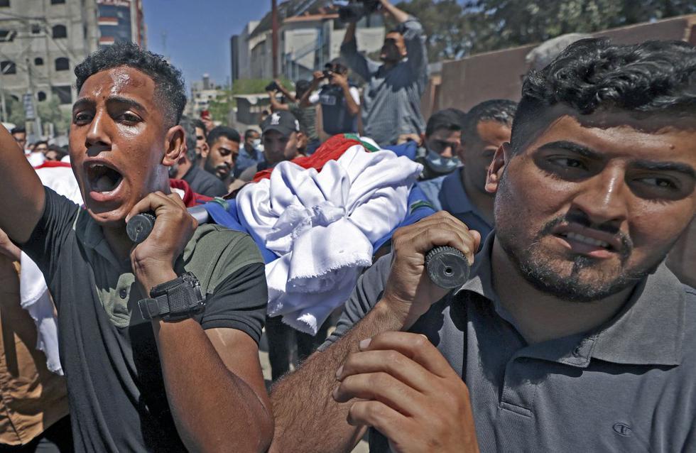 Los deudos palestinos llevan el cuerpo de un miembro de la familia Abu Hatab durante una procesión fúnebre en la ciudad de Gaza. Diez miembros de la familia murieron en un ataque aéreo israelí en el oeste de la Franja de Gaza. (Foto de MAHMUD HAMS / AFP).