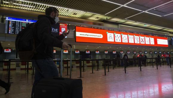 Los pasajeros pasan frente a una pantalla que enumera los vuelos cancelados entre Suiza y Gran Bretaña en el aeropuerto de Ginebra, en Ginebra. (EFE / EPA / SALVATORE DI NOLFI).