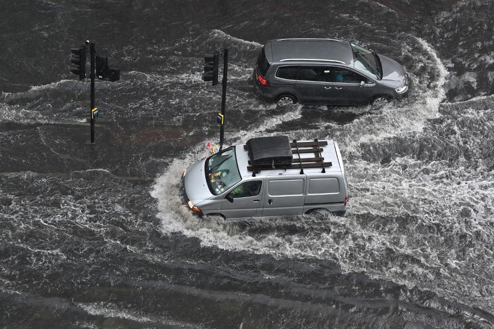 Las lluvias torrenciales en el sureste de Inglaterra anegaron este domingo por la tarde calles de Londres, donde los bomberos recibieron cientos de llamadas. En la foto, los vehículos atraviesan aguas profundas en una carretera inundada en el distrito de The Nine Elms de Londres. (Texto: AFP / Foto de JUSTIN TALLIS / AFP)