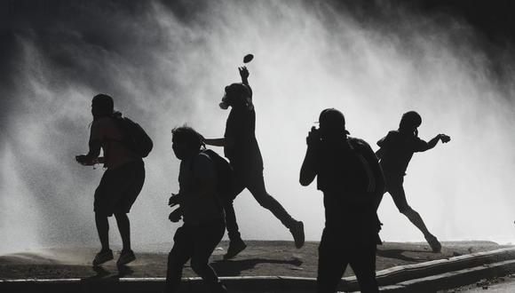 Los manifestantes se enfrentan con la policía de Chile durante una protesta cerca de la Plaza Italia de Santiago. (AP Photo/Fernando Llano).