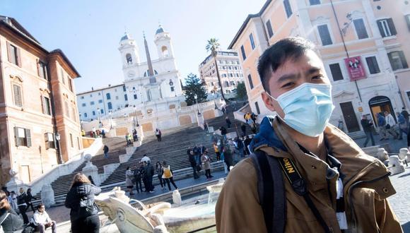 Un turista pasea con mascarilla por la Plaza de España en Roma, Italia. (EFE/Claudio Peri).