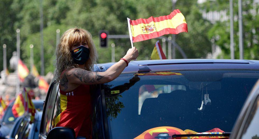 """Una manifestante agita una bandera desde su automóvil mientras participa en una protesta llamada """"Caravana por España y su libertad"""" del partido de extrema derecha Vox. Ellos están en contra de la gestión del gobierno  durante la crisis del coronavirus. (AFP / JAVIER SORIANO)."""