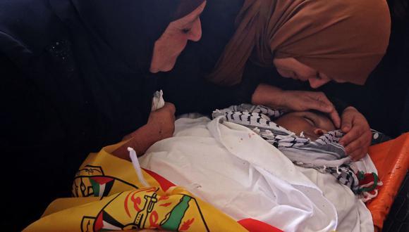 Los familiares lloran durante el funeral del niño palestino Mohamad al-alami en la ciudad de Beit Ummar, al noroeste de Hebrón, el 29 de julio de 2021. (Foto de AHMAD GHARABLI / AFP).