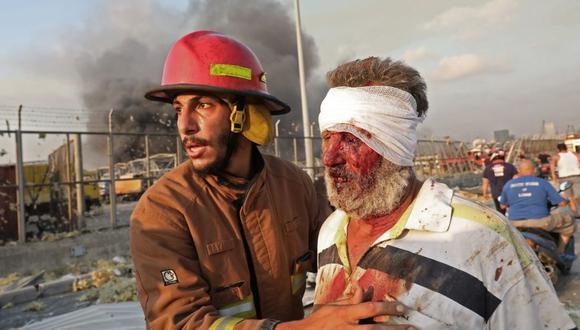 Un hombre herido es ayudado por un bombero cerca de la escena de la explosión en Beirut, Líbano. (Foto por ANWAR AMRO / AFP).