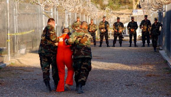 En esta foto publicada el 18 de enero de 2002 por el Departamento de Defensa, la policía militar del Ejército de Estados Unidos lleva a un detenido a su celda en el Campamento Rayos X en Guantánamo. (AFP PHOTO / US NAVY / Shane T.McCOY).