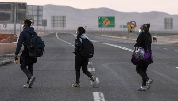 Los migrantes venezolanos Reinaldo (izquierda), Anyier (derecha), y su hija Danyierly caminan por la carretera camino a Iquique, Chile, luego de cruzar desde Bolivia. (Foto de MARTIN BERNETTI / AFP).