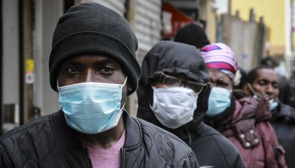Coronavirus en New York | La gente espera una distribución de máscaras y alimentos del reverendo Al Sharpton en el barrio de Harlem, en Nueva York. (Foto AP / Bebeto Matthews).