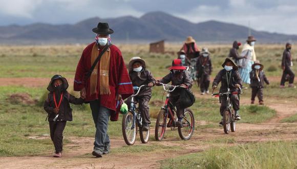 Los padres indígenas aymarás acompañan a sus hijos con uniformes de protección nuevos a la escuela Jancohaqui Tana cuando regresan para su primera semana de clases presenciales en medio de la pandemia de COVID-19 cerca de Jesús de Machaca, Bolivia. (Foto: AP /Juan Karita)