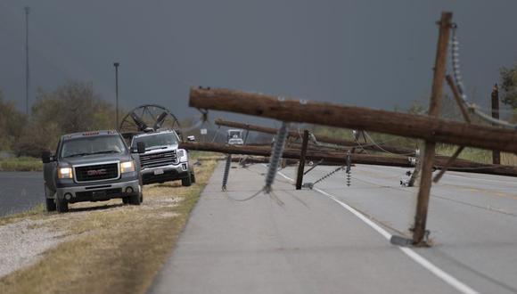 Las personas que intentan llegar a sus hogares en Cameron pasan cerca de líneas eléctricas caídas en la autopista después del paso del huracán Laura al sur de Lake Charles, Louisiana, el 28 de agosto de 2020. (Foto de ANDREW CABALLERO-REYNOLDS / AFP).