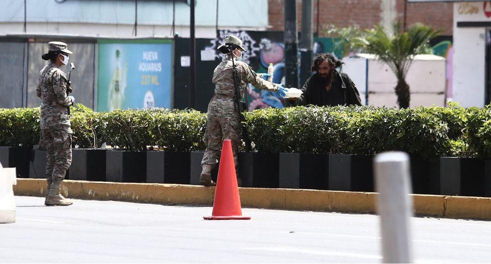 Miembros de las fuerzas armadas en gesto solidario con un indigente en este jueves de cuarentena total en Lima. (Foto: Jesus Saucedo)