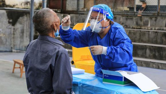 Un hombre (izquierda) se somete a una prueba de ácido nucleico para el coronavirus Covid-19 en Mangshi, en la prefectura autónoma de Dehong Dai y Jingpo, que limita con Myanmar en la provincia de Yunnan, suroeste de China.  (Foto: STR / AFP).