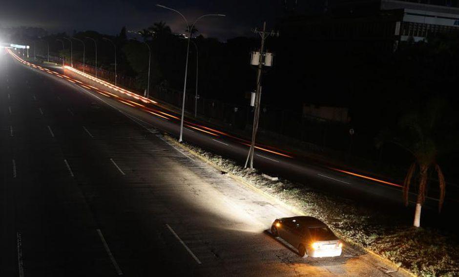 Vista de una carretera iluminada solo por los vehículos que la transitan debido a un apagón este lunes, en Caracas (Venezuela).  Foto: EFE