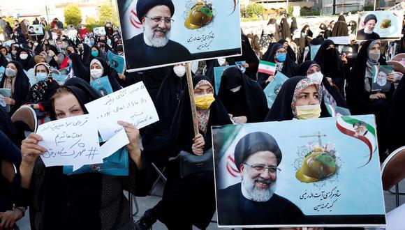 Mujeres simpatizantes del candidato presidencial iraní Ebrahim Raisi sostienen fotografías suyas durante un acto de campaña electoral en Teherán. (EFE / EPA / ABEDIN TAHERKENAREH).