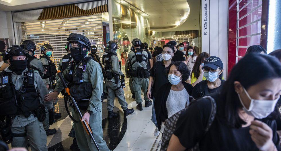 La gente pasa junto a la policía antidisturbios de Hong Kong, que realiza una operación de limpieza durante una manifestación en un centro comercial, en respuesta a la nueva ley de seguridad nacional introducida en la ciudad. (ISAAC LAWRENCE / AFP)