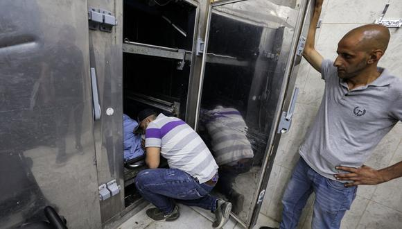 Familiares del agente de inteligencia militar palestino Taysir Issa, quien fue asesinado en un enfrentamiento con las fuerzas especiales israelíes, lloran junto a su cuerpo en la morgue de un hospital en Yenín, en el norte de la Cisjordania, el 10 de junio de 2021. (Foto de JAAFAR ASHTIYEH / AFP).