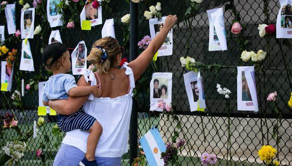 Victoria Mayer y su hijo Antonio visitan un memorial improvisado cerca del derrumbado edificio en Surfside, Florida, al norte de Miami Beach. (Foto de Andrea SARCOS / AFP).