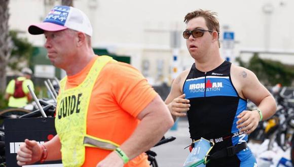 Chris Nikic mientras corre junto a su acomompañante guía en el triatlón. (Foto: Facebook | Ironman Florida)