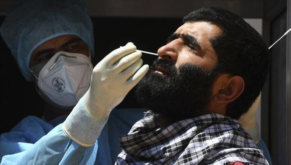 Un trabajador de la salud toma una muestra de un hisopo nasal de un hombre para realizar la prueba del coronavirus en Srinagar (India), el 2 de junio de 2021. (TAUSEEF MUSTAFA / AFP).