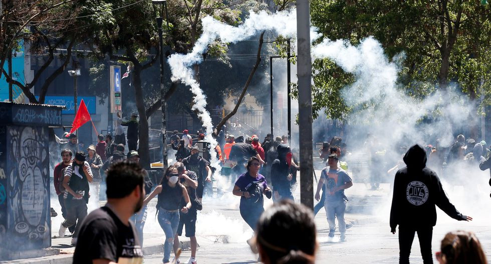 Protesters run from tear gas as they clash with security forces during a protest against Chile's state economic model in Valparaiso, Chile, October 21, 2019. REUTERS/Rodrigo Garrido