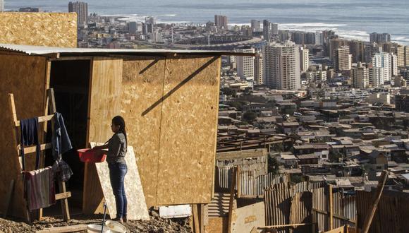 Una mujer está frente a su precaria casa en un campamento en Altamira, Antofagasta, Chile. (Foto de GLENN ARCOS / AFP).