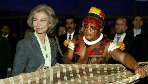 La Reina Sofía de España escucha una explicación sobre la artesanía indígena del cacique Aritana de la tribu Yawalapiti de la región del Alto Xingu (norte de Brasil), el 6 de octubre de 2003 en Brasilia. El líder indígena murió por coronavirus. (Foto: EVARISTO SA / AFP).