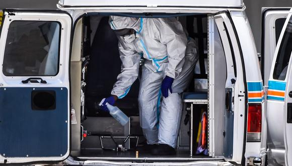 Personal médico desinfecta la ambulancia después de trasladar a un paciente al Hospital de Coral Gables, donde son tratados enfermos de coronavirus. (Foto de CHANDAN KHANNA / AFP).