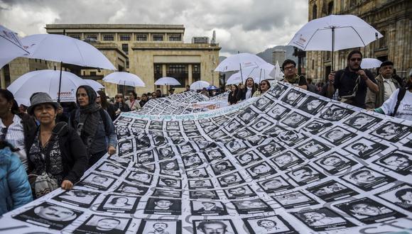 Imágenes de personas desaparecidas y víctimas del conflicto armado se muestran durante una protesta frente al teatro Colón en Bogotá en noviembre del 2017. (Foto referencial / Raúl Arboleda / AFP)