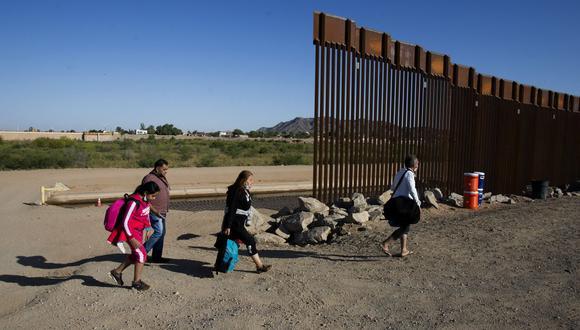 Migrantes de Colombia cruzan la frontera de Estados Unidos y México para entregarse a las autoridades el 13 de mayo de 2021 en Yuma, Arizona. (Foto de RINGO CHIU / AFP).