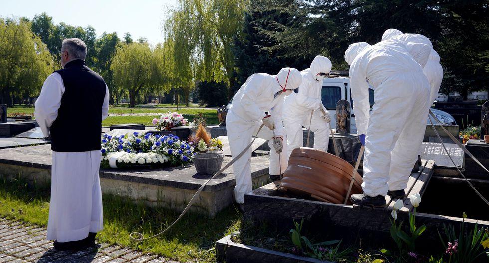 El padre Marcos Rad oficia el funeral mientras los trabajadores municipales que usan equipo de protección bajan el ataúd de una víctima de coronavirus (COVID-19) en el cementerio de El Salvador en Vitoria, España.( REUTERS / Vincent West).