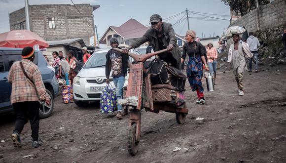 Un hombre lleva equipaje en una bicicleta tradicional de madera mientras los residentes de Goma huyen ante al temor de una erupción del volcán Nyiragongo. (Foto de Guerchom NDEBO / AFP).