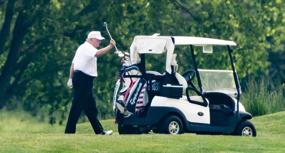 El presidente de Estados Unidos, Donald Trump, con un sombrero y una camisa polo blanca, juega al golf en el Trump National Golf Club en Sterling, Virginia. (EFE/EPA/JIM LO SCALZO).