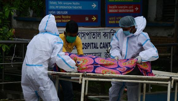 Personal sanitario traslada el cadáver de una persona que murió debido al coronavirus Covid 19 en el hospital del distrito de Siliguri, en la India (Foto de Diptendu DUTTA / AFP).