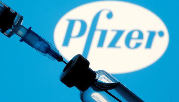 En esta ilustración tomada el 11 de enero de 2021, se ven un frasco y una jeringa frente a un logotipo de Pfizer. (REUTERS/Dado Ruvic).