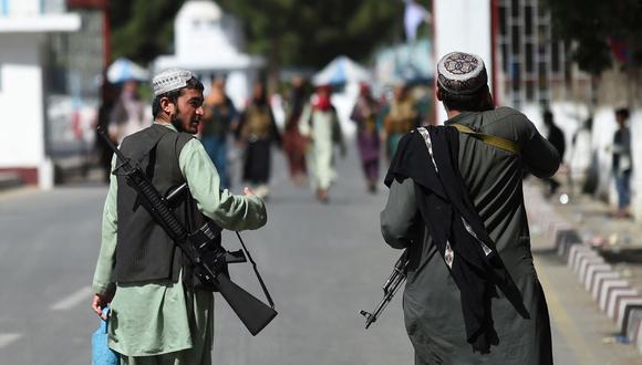 Combatientes talibanes caminan por la puerta de entrada principal del aeropuerto de Kabul, capital de Afganistán, el 28 de agosto de 2021. (WAKIL KOHSAR / AFP).