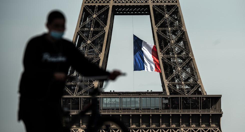 Un hombre con una máscara facial empuja su bicicleta en Trocadero Plaza mientras una bandera nacional francesa ondea en la Torre Eiffel en el fondo el pasado 11 de mayo de 2020, en el primer día de la flexibilización de las medidas de bloqueo en Francia para frenar la propagación del COVID-19. (Foto por PHILIPPE LOPEZ / AFP)