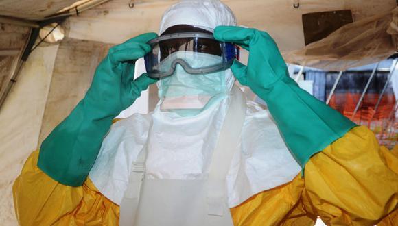 Esta foto de archivo tomada el 15 de agosto de 2014 muestra a un trabajador médico de MSF revisando su ropa protectora en un espejo en Kailahun, epicentro del peor brote de ébola del mundo. (Foto de CARL DE SOUZA / AFP).