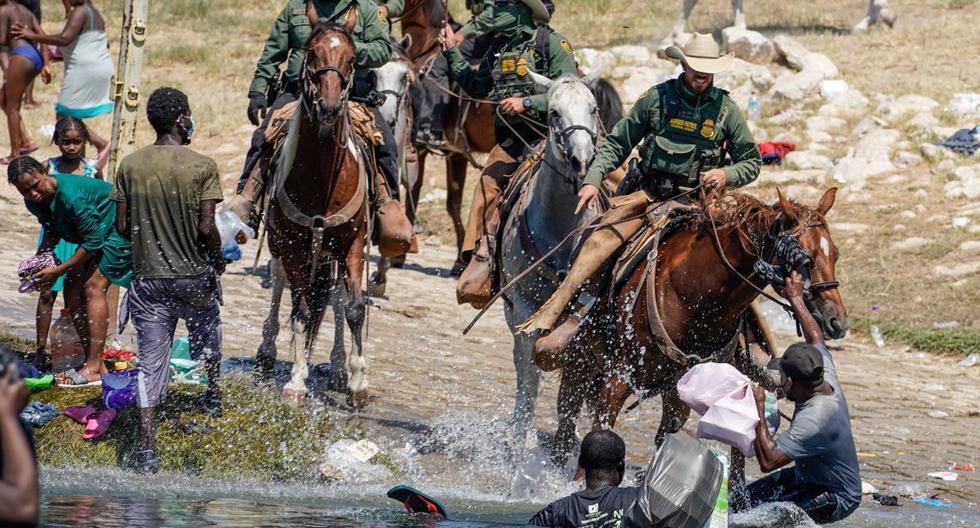 Agentes de la Patrulla Fronteriza de Estados Unidos a caballo intentan evitar que los migrantes haitianos ingresen a un campamento a orillas del Río Bravo, cerca del Puente Internacional Acuña del Río, en Texas, el 19 de septiembre de 2021. (PAUL RATJE / AFP).