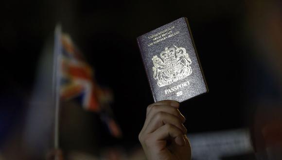 Una persona muestra un pasaporte británico durante una manifestación pidiendo apoyo de Reino Unido, frente al Consulado General Británico de Hong Kong, China, el 23 de octubre de 2019. (EFE/EPA/LYNN BOBO).