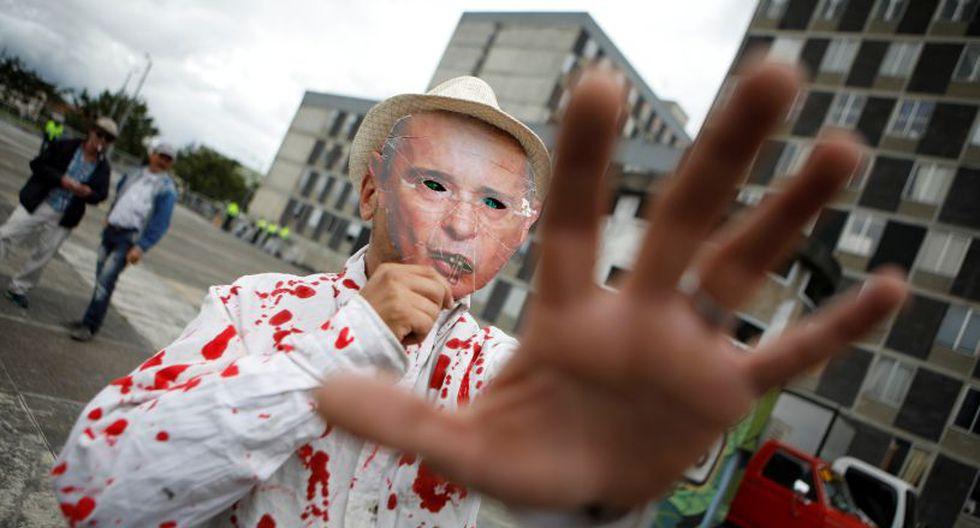 Un partidario de la oposición usa una máscara que representa al ex presidente colombiano Álvaro Uribe mientras se reunía para participar en una manifestación el día de la toma de posesión de Ivan Duque | Foto: Reuters
