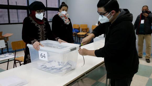Trabajadores electorales con máscaras protectoras abren una urna con votos durante el referéndum sobre una nueva Constitución chilena, en Valparaíso, el pasado domingo 25 de octubre. (Reuters/Rodrigo Garrido).