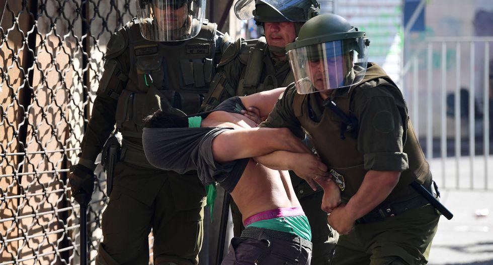 Un manifestante es detenido por la policía en Santiago. (Photo by Martin BERNETTI / AFP).