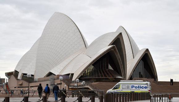 """Una camioneta de la policía permanece dentro de las instalaciones de la Ópera en Sídney el 23 de julio 2021, en medio de un brote de coronavirus que se ha convertido en una """"emergencia nacional"""". (Foto de Saeed KHAN / AFP)."""
